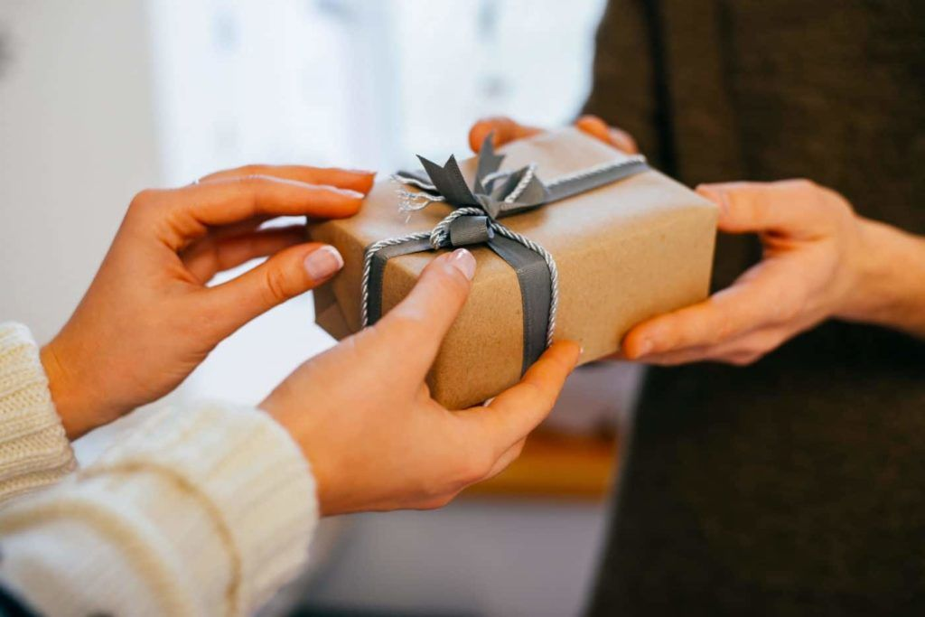 Young woman gives a gift in a box
